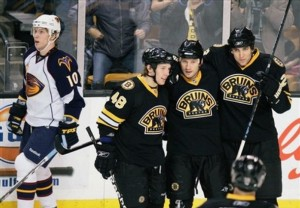 Boston Bruins'  Michael Ryder, second from right, celebrates his goal with teammates Blake Wheeler, right, and  Matt Hunwick (48) as Atlanta Thrashers' Bryan Little (10) skates past in the first period of an NHL hockey game, Saturday, Dec. 13, 2008, in Boston. (AP Photo/Michael Dwyer)