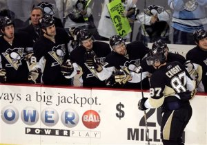 Pittsburgh Penguins' Sidney Crosy (87) is greeted by teammates after scoring his third goal of the game against the New Jersey Devils in a NHL hockey game in Pittsburgh Saturday, Nov. 29, 2008. The Penguins won 4-1. (AP Photo/Gene J. Puskar)