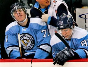 Pittsburgh Penguins' Evgeni Malkin, left, of Russia grimaces after being slashed against the Toronto Maple Leafs in the first period of a NHL hockey game  in Pittsburgh Saturday, Dec. 20, 2008. The Maple Leafs won 7-3. At right is Penguins' Sidney Crosby. (AP Photo/Gene J. Puskar)