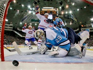 Pittsburgh Penguins' goalie Marc-Andre Fleury (29) can't make the save on a first period goal by Montreal Canadiens' Andrei Kosititsyn, center rear, of Belarus as Canadiens Alex Kovalev, left rear, of Russia celebrates during a NHL hockey game in Pittsburgh Saturday, Dec. 27, 2008.(AP Photo/Gene J. Puskar)