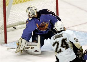 Pittsburgh Penguins' Matt Cooke (24) slips the puck past Atlanta thrashers goalie Ondrej Pavelec, of the Czech Republic, in the first period of an NHL hockey game Thursday, Dec. 18, 2008, in Atlanta.  (AP Photo/John Bazemore)