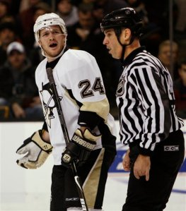 Pittsburgh Penguins' Matt Cooke (24) is escorted to the penalty box after being called for goaltender interference during the third period of their 4-2 loss to the Boston Bruins in a hockey game in Boston, Thursday, Jan. 1, 2009. (AP Photo/Winslow Townson)
